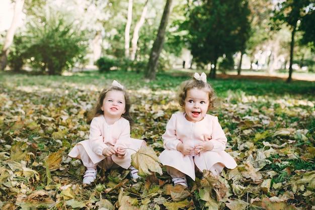 Irmãzinhas bonitinha brincando em um parque de primavera