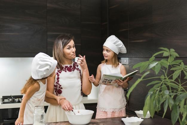 Irmãzinhas bonitos olhando para sua mãe, degustação de comida na cozinha