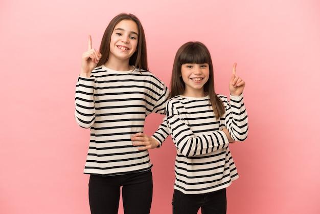 Irmãzinhas isoladas em um fundo rosa, mostrando e levantando um dedo em sinal dos melhores