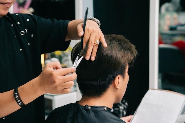 Irreconhecível cabeleireiro masculino, dando o corte de cabelo do cliente no salão