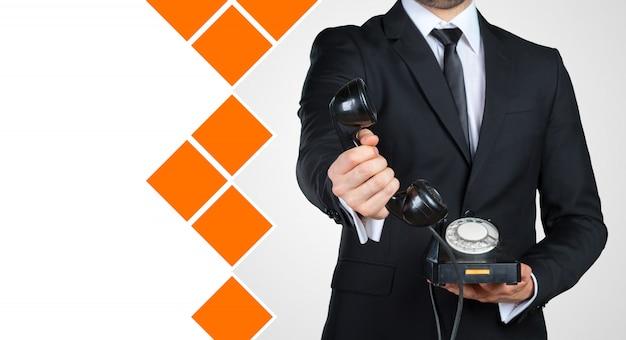 Irreconhecível empresário segurando um receptor de telefone vintage