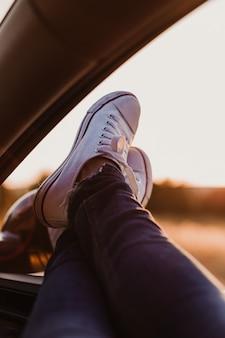 Irreconhecível garota moderna hipster relaxando em um carro. pés do lado de fora da janela ao pôr do sol. conceito de viagens
