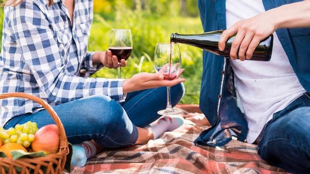 Irreconhecível homem derramando vinho em copos durante a data