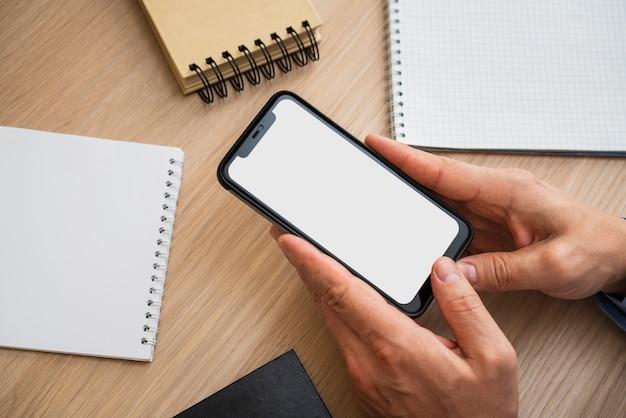 Irreconhecível homem segurando o telefone em branco