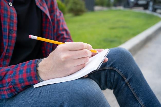 Irreconhecível homem sentado na calçada da estrada e escrevendo na nota