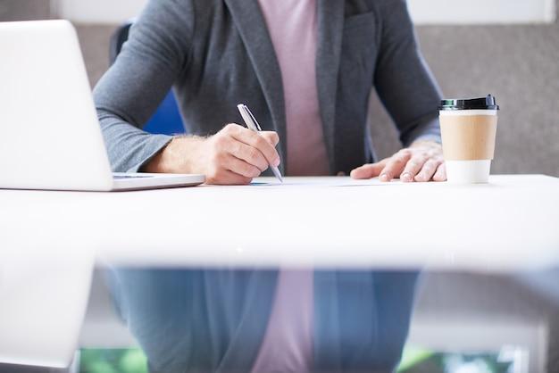Irreconhecível homem sentado na mesa no escritório e escrever