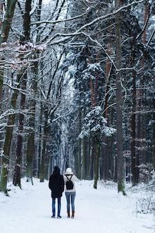 Irreconhecível jovem casal em pé sozinho e olhando para um caminho em uma floresta de inverno. vista de trás