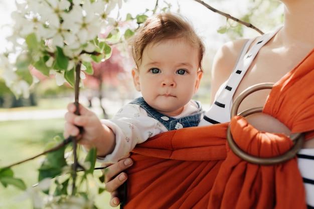 Irreconhecível jovem mãe com seu bebê infantil no sling
