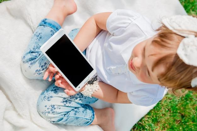 Irreconhecível menina com tablet, vestida de pólo branco e calça jeans, descalça, sentado na capa branca no parque, vista superior.