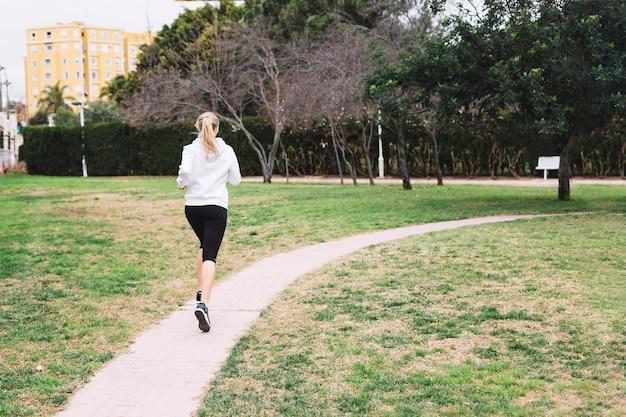 Irreconhecível mulher correndo no parque