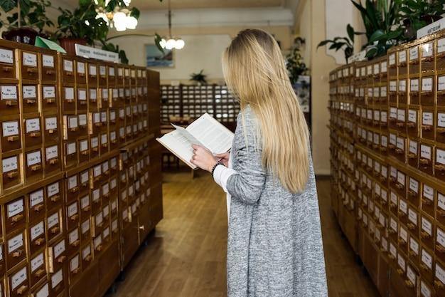 Irreconhecível mulher lendo na biblioteca