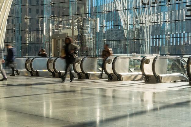 Irreconhecível passageiro e turista andando até a escada rolante