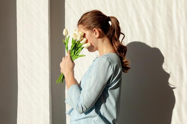 Irreconhecível senhora segurando tulipas brancas