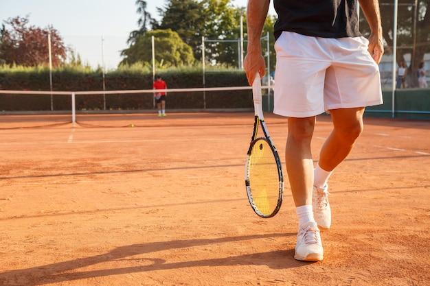 Irreconhecível tenista profissional andando na quadra de tênis em dia ensolarado.