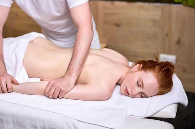 Irreconhecível terapeuta masculino massageando ruiva com mulher atraente e vista lateral