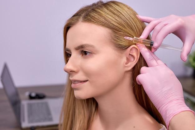 Irreconhecível tricologista médica conduz mesoterapia ou terapia de plasma para paciente jovem. tratamento da alopecia.
