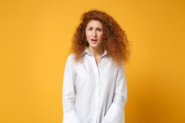 Irritada, chocada, cansada, jovem ruiva, vestindo uma camisa branca casual posando isolada em uma parede amarelo-laranja