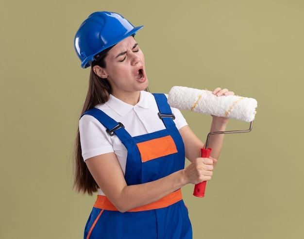 Irritada com os olhos fechados, jovem construtora de uniforme segurando uma escova giratória isolada na parede verde oliva
