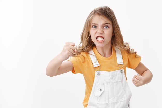Irritada, descontente e angustiada garotinha loira odiosa, criança olhando furiosa e chateada, reclamando, fazendo careta incomodada luta intensa, parece chateada gesticulando, punho cerrado, parede branca de pé