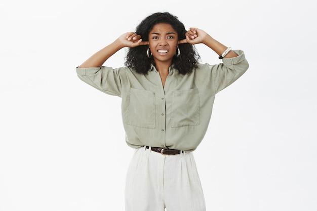 Irritada, descontente e irritada, jovem atraente empresária de pele escura se sentindo incomodada por um som alto e irritante