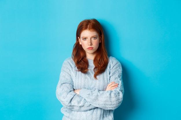 Irritada e incomodada, a garota ruiva teeange cruza os braços no peito, olhando para algo chato e chato, de pé contra um fundo azul.