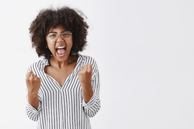 Irritada, irritada, mulher afro-americana, gerente de escritório com blusa listrada e óculos cerrando os punhos com emoções raivosas, gritando e mostrando que está farto de um colega estúpido