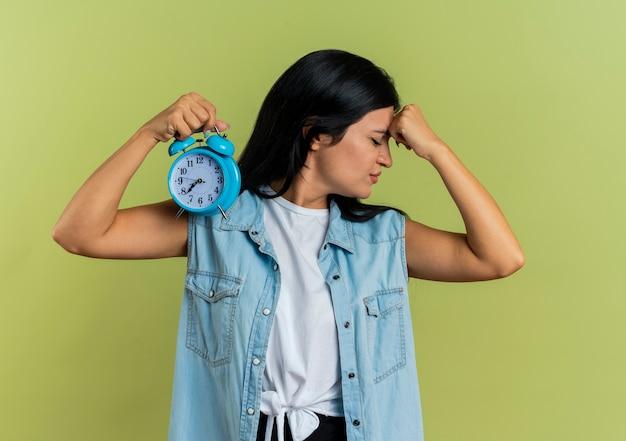 Irritada, jovem caucasiana coloca o punho na testa e segura o despertador isolado em um fundo verde oliva com espaço de cópia