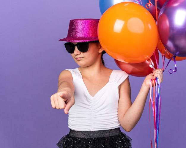 Irritada jovem caucasiana de óculos de sol com chapéu de festa violeta segurando balões de hélio e apontando isolada na parede roxa com espaço de cópia