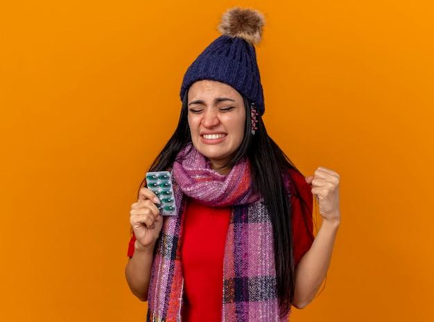 Irritada, jovem caucasiana doente com chapéu de inverno e lenço segurando o pacote de cápsulas com outros pacotes sob o chapéu cerrando o punho com os olhos fechados, isolado na parede laranja com espaço de cópia