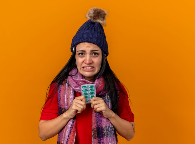 Irritada, jovem caucasiana doente com chapéu de inverno e lenço segurando um pacote de cápsulas com outros pacotes sob o chapéu isolado na parede laranja com espaço de cópia