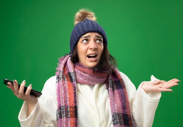 Irritada, jovem caucasiana doente usando um manto de inverno, chapéu e lenço segurando um celular e um guardanapo, olhando para cima, isolado na parede verde