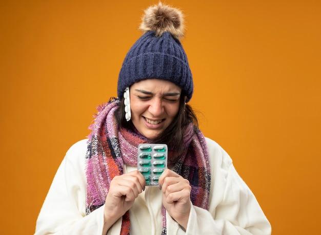 Irritada, jovem caucasiana doente vestindo um manto de inverno, chapéu e lenço segurando um pacote de cápsulas com um pacote de comprimidos sob o chapéu com os olhos fechados, isolado na parede laranja