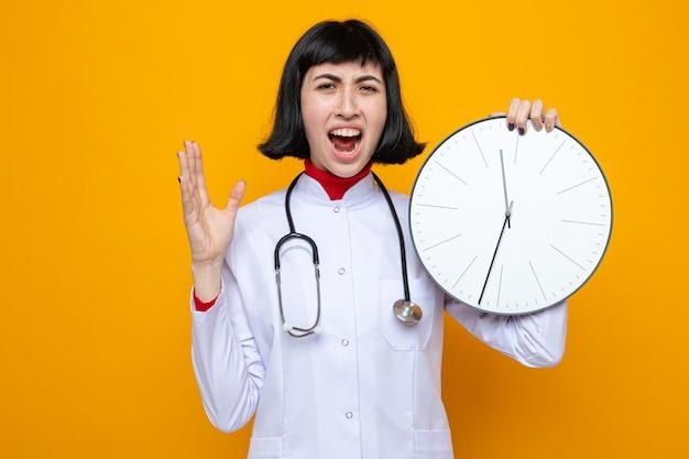 Irritada, jovem e bonita caucasiana com uniforme de médico com estetoscópio segurando o relógio e mantendo a mão aberta