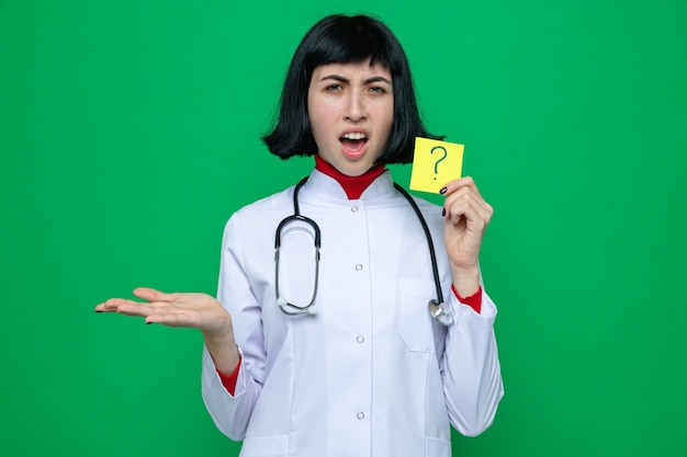 Irritada, jovem e bonita caucasiana com uniforme de médico com estetoscópio segurando um bilhete de perguntas e mantendo a mão aberta
