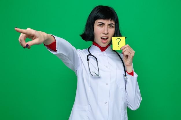 Irritada, jovem e bonita caucasiana com uniforme de médico com estetoscópio segurando um cartão amarelo com o sinal de interrogação e apontando para o lado