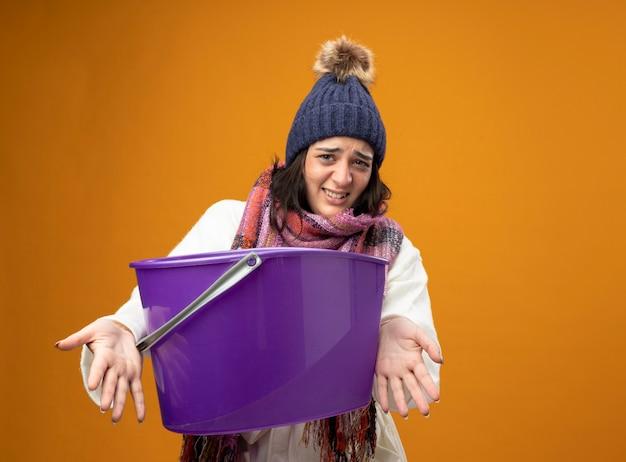 Irritada, jovem mulher doente usando um manto de inverno, chapéu e lenço, tendo náuseas, estendendo o balde de plástico para a frente, olhando para a frente, isolado na parede laranja