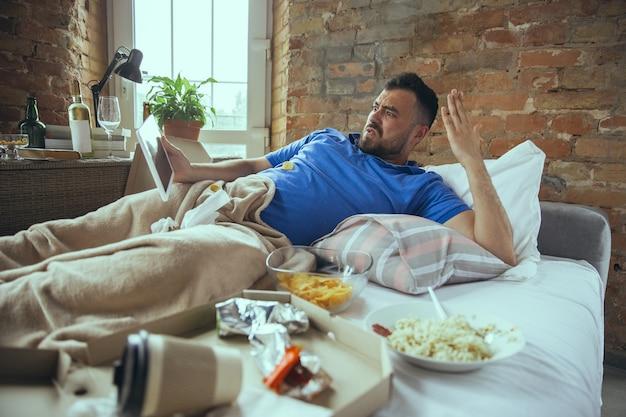 Irritado assistindo tablet homem caucasiano preguiçoso morando em sua cama cercado de bagunça