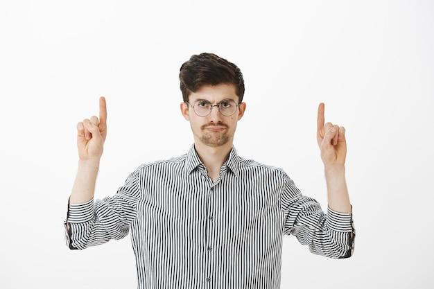 Irritado, descontente e atraente modelo masculino com bigode e barba em óculos redondos, levantando o dedo indicador e apontando para cima com olhar desapontado e incomodado