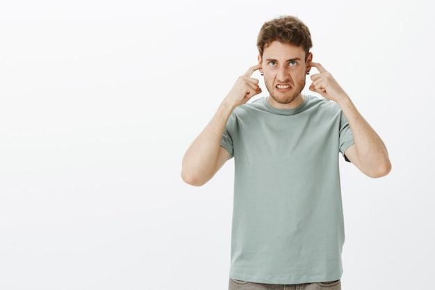 Irritado, irritado, homem atraente com cabelo claro, fazendo careta de raiva, cobrindo as orelhas com os dedos indicadores