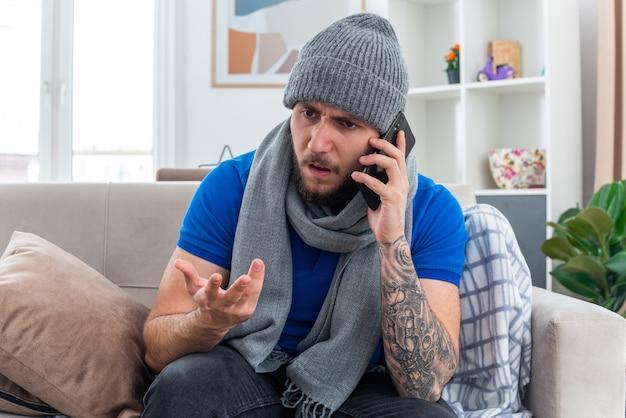 Irritado, jovem, doente, usando lenço e chapéu de inverno, sentado no sofá na sala, olhando para o lado, falando no telefone, mostrando a mão vazia