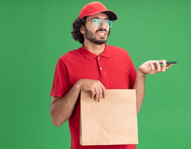 Irritado, jovem entregador, caucasiano, de uniforme vermelho e boné, usando óculos, segurando um pacote de papel e um telefone celular