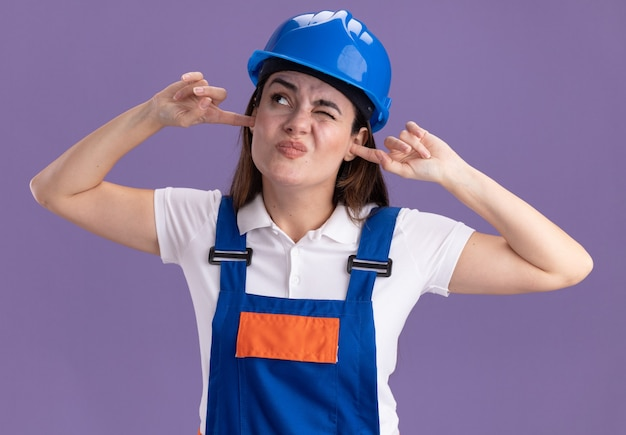 Irritado, olhando para as mulheres jovens construtoras em uniforme de orelhas fechadas isoladas na parede roxa