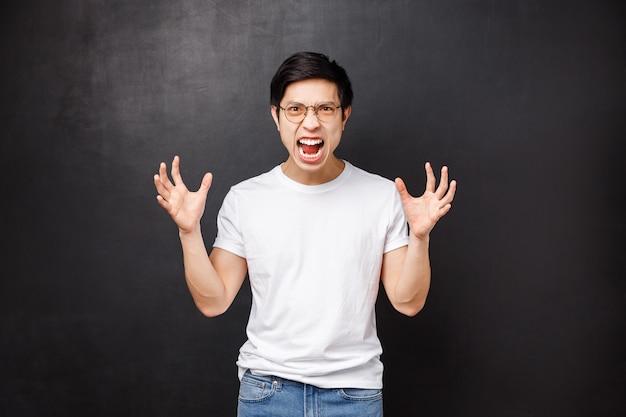 Irritado, tenso, homem asiático puto ficando louco de raiva e ódio