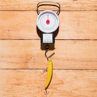 Isca de pesca amarela pendurado na escala de medição sobre a mesa de madeira