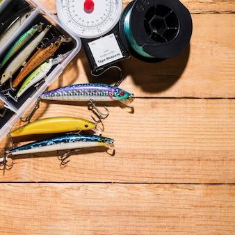 Isca de pesca colorida com escala de medição e carretel de pesca na mesa de madeira
