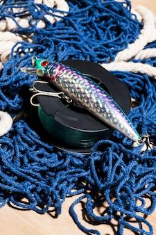 Isca de pesca com gancho; carretel de pesca na rede de pesca azul na superfície de madeira
