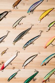 Iscas de pesca coloridas diagonais na superfície de madeira