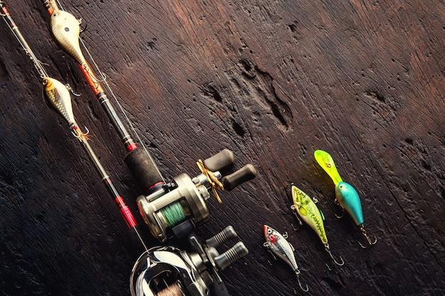 Iscas de pesca, ganchos e acessórios em escurecer o fundo de madeira