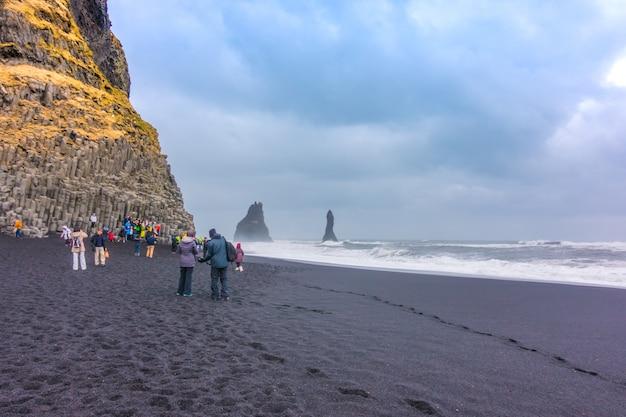 Islândia - 15 mar - turista desfrutando na praia de reynisfjara, no sul da islândia em feriados de fim de semana, em 15 de março de 2017.