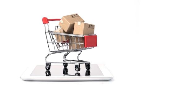 Isolado de caixas de papel de transporte dentro do carrinho vermelho do carrinho de compras no tablet isolado no branco.